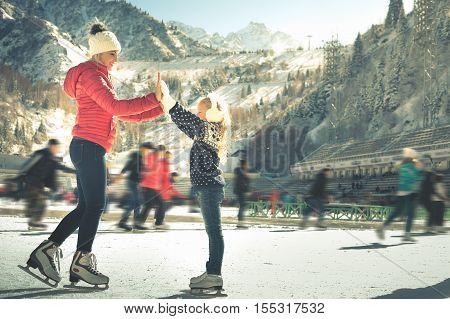 Happy family outdoor ice skating at rink. Mother and daughter has winter activities. Mom, kids. Medeo stadium. Almaty.