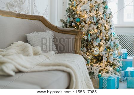 Christmas or new year decoration at Living room interior and holiday home decor concept. Calm image of blanket on a vintage sofa with tree and gifts. Selective focus.