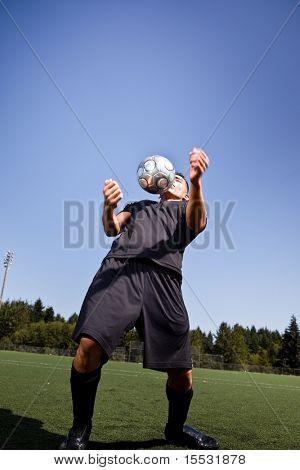 A shot of a hispanic soccer or football player controlling the ball with his chest