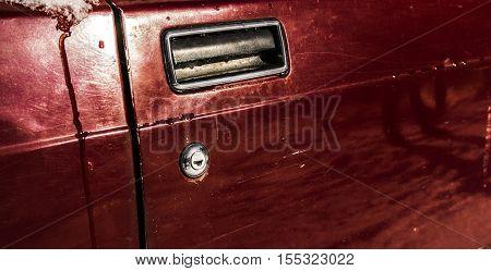 Handle of red car door, old car door, automotive background, car door detail