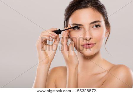 Woman applying black mascara on eyelashes with makeup brush. Young beautiful woman applying mascara makeup on eyes by brush. Portrait of brunette beauty girl applying makeup over grey background.