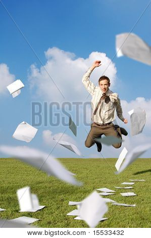 A businessman in a field jumping with his paperwork flying around him.