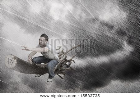 A young male rushing on a witches broomstick in terrible weather high in the sky.
