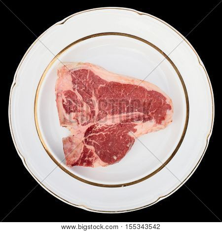 Raw T-bone steak on a rustic plate, isolated on black background