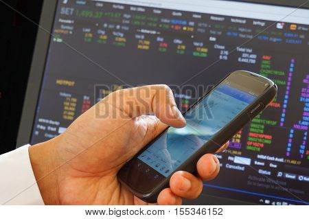 Male trader use smart phone sitting in office.