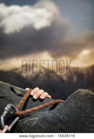 A rockclimber's hand on the final ledge.