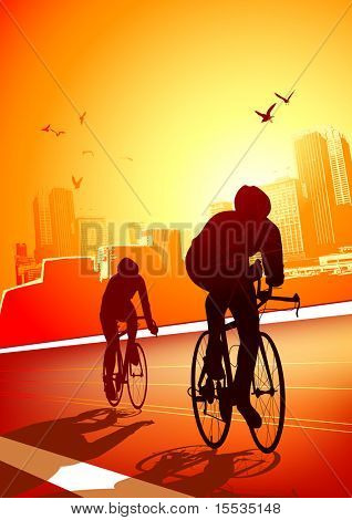Two cyclists riding on a warm sunny evening with the city in the background.