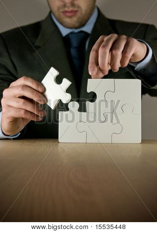 A businessman making a puzzle.