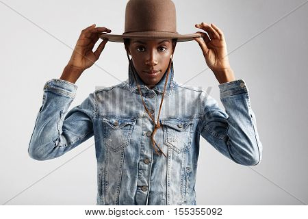 black woman puts hat on watching at camera