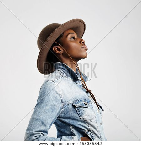 black woman in hat in profile on grey