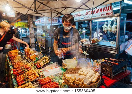 CHIANG MAI THAILAND - AUGUST 27: Young man sells satay at the Saturday Night Market on August 27 2016 in Chiang Mai Thailand.