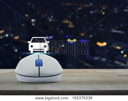 Wireless computer mouse with car front view flat icon on wooden table over blur light city tower Internet service car concept