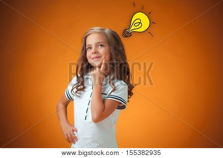 The cute cheerful little girl portrait on orange background. Concept of discovery