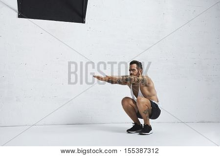 Strong tattooed in white unlabeled tank t-shirt male athlete shows calisthenic moves Squat calf rises, low position