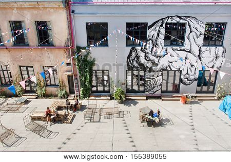 TBILISI, GEORGIA - OCT 9, 2016: Young people ralxing in urban part of city with artistic galleries and weird benches around on October 9, 2016. Tbilisi has a population of 1.5 million people