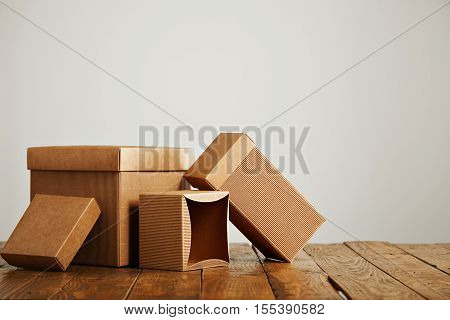 Set of three unlabeled similar craft cardboard boxes with covers beautifully arranged in a studio with white walls