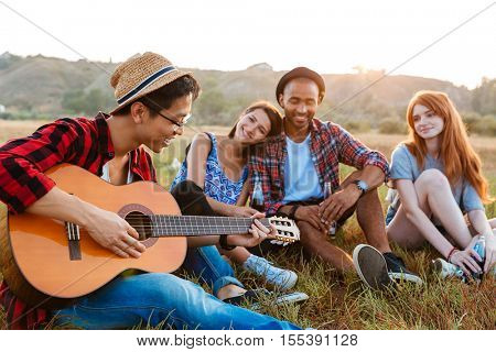 Group of happy relaxed young people drinking beer and playing guitar outdoors