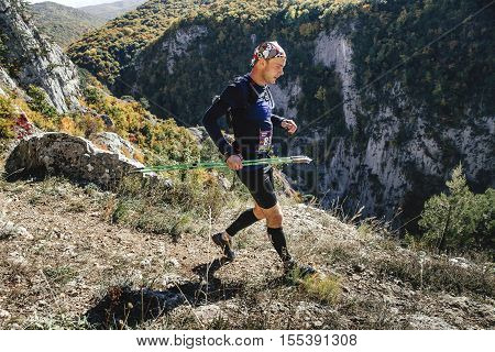 Yalta Russia - October 6 2016: young male runner with walking poles running through steep cliff during Crimea mountain marathon