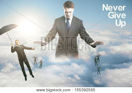 Pensive young businessman controlling subordinates on sky background with sunlight. Manipulation concept