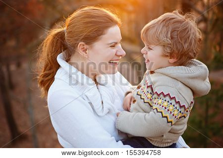 Mother and little son in park or forest, outdoors. Hugging and having fun together. Happy toddler boy and young mum, kid and woman playing.