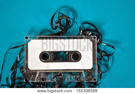cassette tape on turquoise painted wood with unraveled tape
