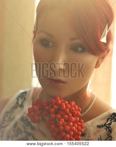 The Redhead Woman In The Sunlight With Orange Wild Ash Berries