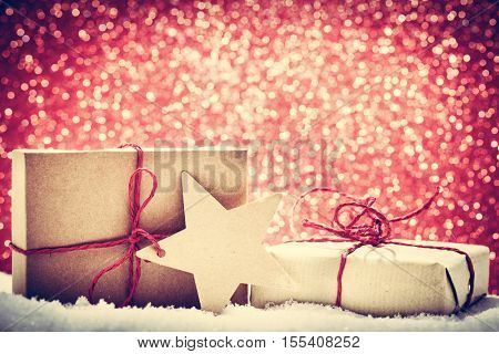 Retro rustic Christmas gifts, presents in snow on glitter background. Handmade eco paper wrap.