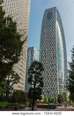 Tokyo Japan - October 2 2016: The glass-and-iron iconic Cocoon-shaped tower or Tokyo Mode Gakuen from top to bottom under blue sky. Green foliage and other towers. Shinjuku neighborhood.