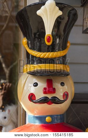 Close up of the face of a toy soldier and Christmas icon with mustache and plumed helmet during the winter holidays