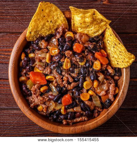 Chili con carne in bowl with tortilla chips on wooden background.