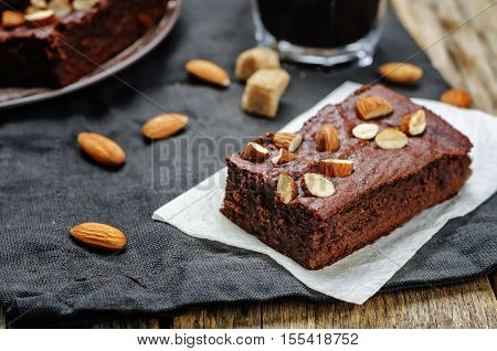 Almond butter brownies dates with almonds on wood background