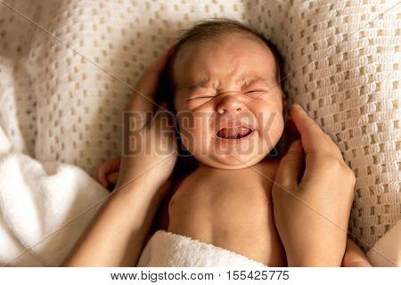 newborn baby boy crying in his crib. Newborn baby boy in bed.