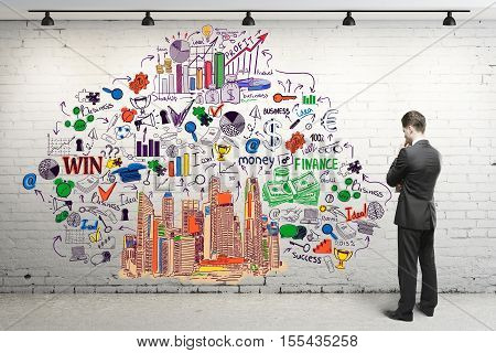 Thoughtful young man in suit looking at white brick wall with creative business sketch. Research concept