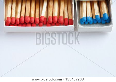 Open matchstick boxes. Red, blue heads on white paper background. Macro view