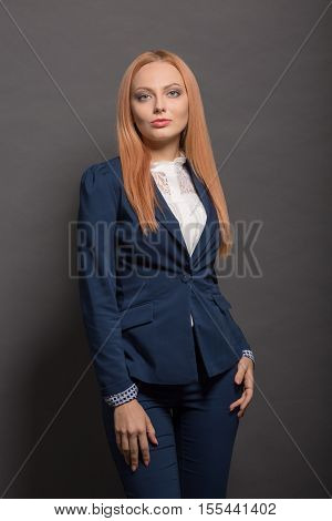 Portrait of professional red haired young model looking for camera while posing isolated on grey background in studio. Fashion or vogue concept.