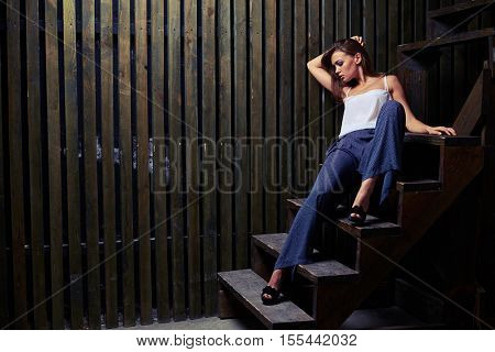 Mid side shot of full-relaxed female with a magnificent face with cheekbone sitting on the stairs in a stylish suit in studio. Concept of rest, carefree and self-contained