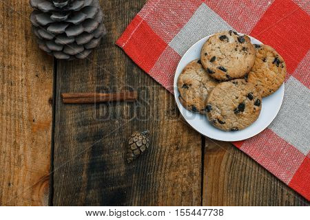 Chocolate Cookies In A White Plate On A Checkered Tablecloth On Wooden Background. Near Cones And Ci