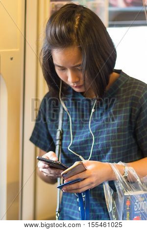 BANGKOK, THAILAND, SEPTEMBER 23, 2016 : A woman is using three smartphones at the same time inside the public transportation in Bangkok, Thailand