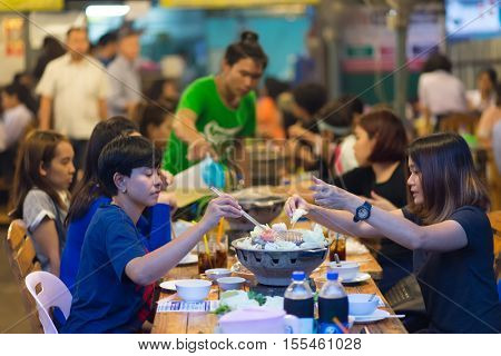 BANGKOK, THAILAND, SEPTEMBER 23, 2016 : People having traditional Thai Mookata barbecue in a Bangkok restaurant, Thailand