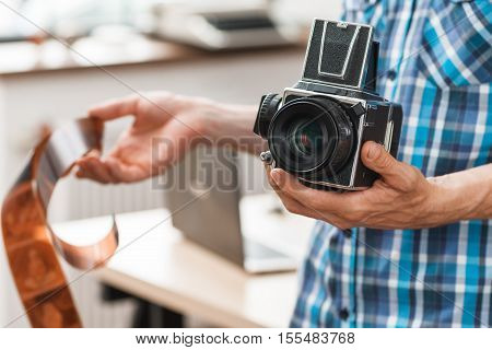 Photographer standing with retro medium format camera and negative film. Unrecognizable man holding old fashioned photographing equipment. Electronic development, technology evolution, hobby concept
