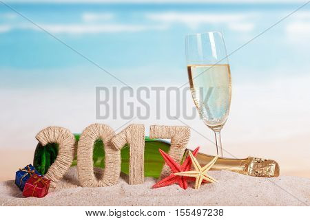 Figures 2017, a bottle of champagne and glass, starfish, gifts in the sand against the sea.