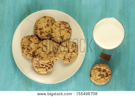 A photo of a plate of freshly baked chocolate chips cookies, shot from above on a vibrant blue background, with a glass of milk and a piece of chocolate