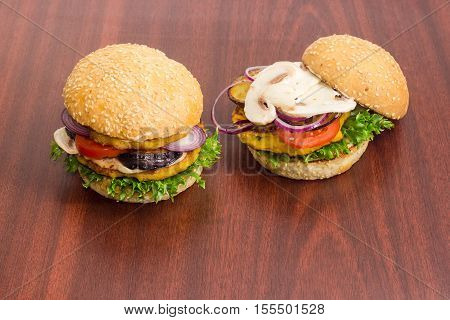 Two vegetarian burger with filling of two lentil patties lettuce tomato onion eggplant mushrooms and condiments on a dark wooden surface