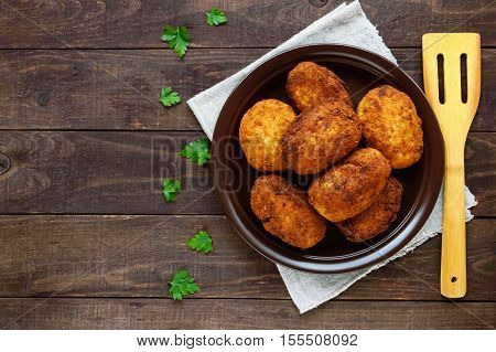 Meat mini-rolls (cutlet) with boiled egg in a clay bowl on dark wooden background. The top view.