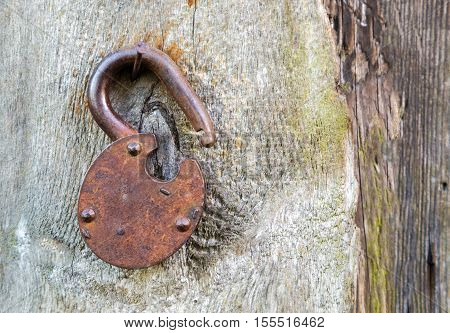 The Old rusted metal lock on a wooden surface retro style close-up