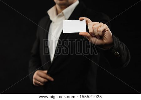 The businessman in black costume showing empty credit card or visiting card, close up