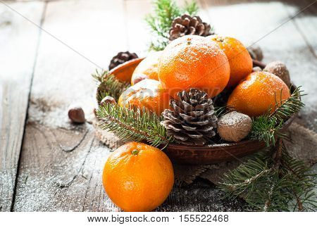 Tangerines fir tree brunches pinecones and nuts. Christmas food decorations. Table setting