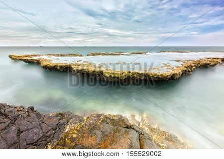 Wonderful seascape with sea waves hitting large rock formed soft sheet like a cascade of water floating in the morning to greet the new day