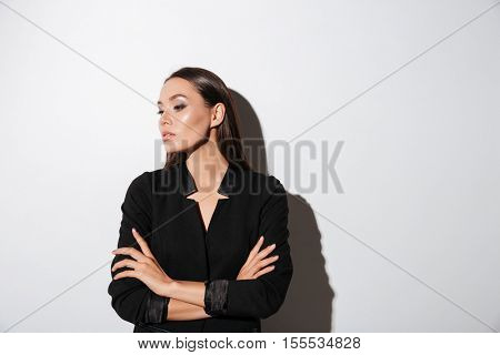 Young brunette woman in black suit standing with arms folded over white background
