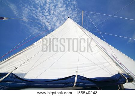 Big white sail of modern yacht sailing on river at summer sunny day